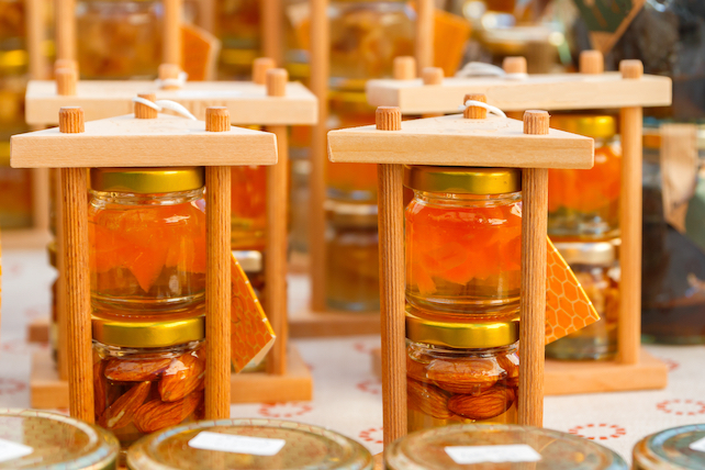honey-and-almonds-in-two-jars-on-top-of-each-other-in-wooden-frame