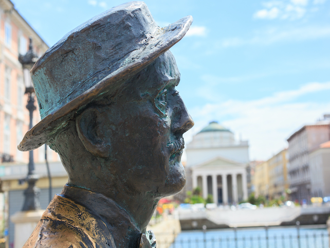 A bronze sculpture of James Joyce with a building in the backgorund