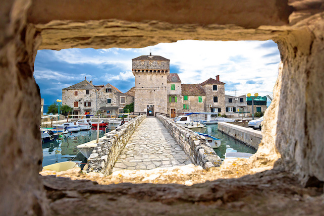 view-of-Kastel-Gomilica-through-a-cut-out-stone-on-the-opposite-side