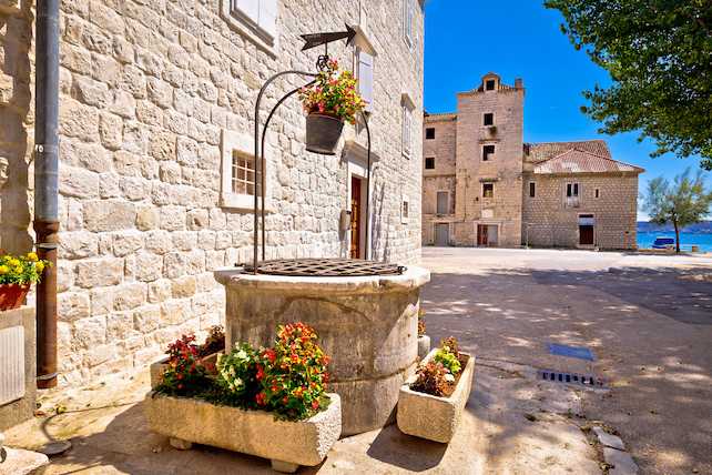 an-old-stone-well-surrounded-by-flowers-and-a-street-with-acces-to-sea