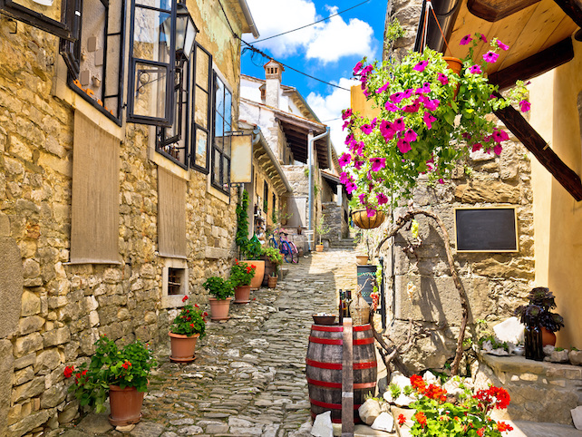 open-windows-in-a-narrow-street-full-of-colorful-flowers-in-Hum-in-Istria