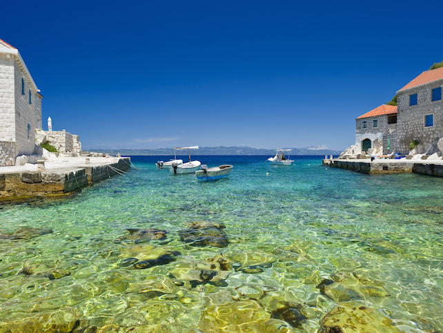 Little fisherman's port with stone houses and a few boats in cristal clear sea