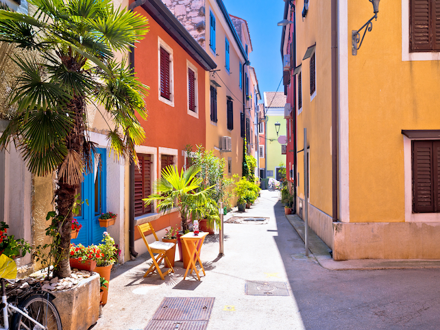 colourful-houses-in-a-row-with-flowers-and-chairs-outside-in-Novigrad