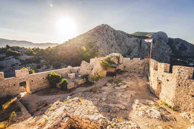 ruins-of-an-old-fortress-and-a-flag-located-high-on-top-of-a-hill-in-omis-dalmatia