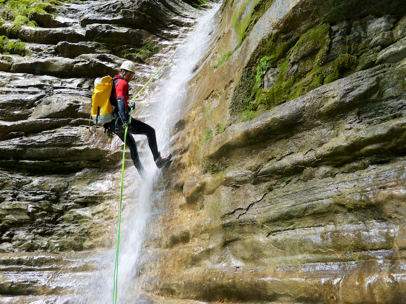 a man with equipment on a rope climbing down a steep cliff with waterfall