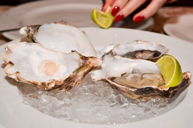 a portion of oysters-served-on-a-white-plate-with lime
