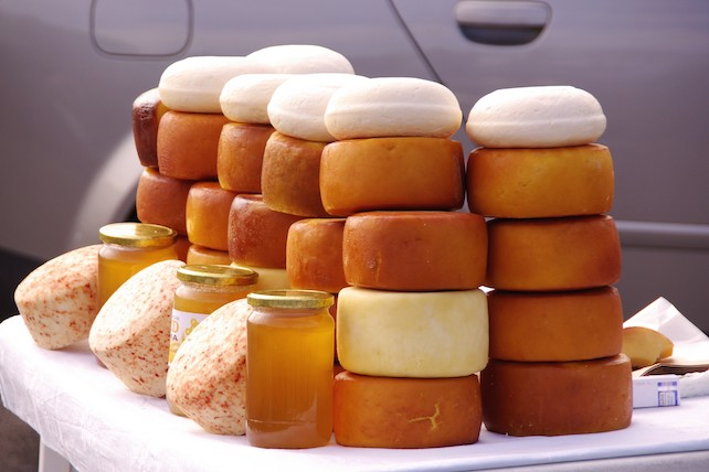 rolls-of-yellow-and-orange-pag-cheese-on-top-of-one-another-for-sale