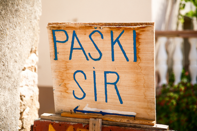 a-wooden-board-with-a-sign-that-says-paski-sir-written-in-blue-letters