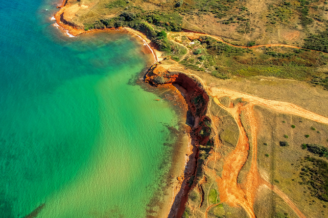 areal-view-of-a-sandy-beach-with-turquise-see-and-red-rocks-on-the-other-side