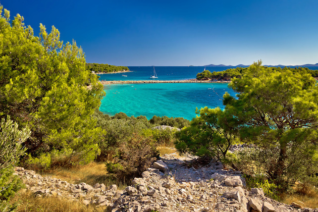 view-from-a-rocky-path-on-to-a-peacefull-cove-and-emerald-sea-water