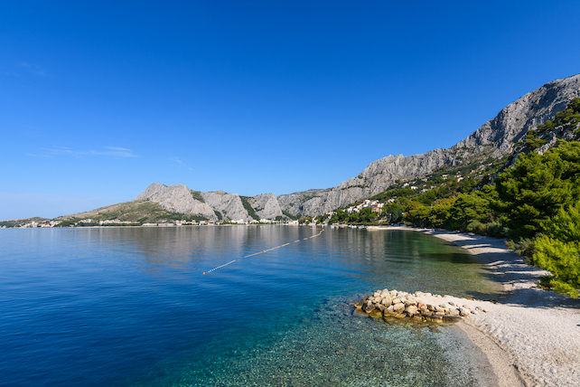 view-of-a-promenade-by-the-sea-with-mountains-and-city-of-Omis-in-background