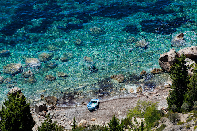view-from-above-on-a-small-blue-boat-on-the-beach-and-clear-sea-water-behind-it
