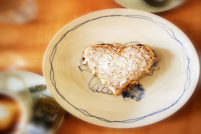 a-slice-of-rab-cake-in-a-heart-shape-on-a-small-decorative-white-plate