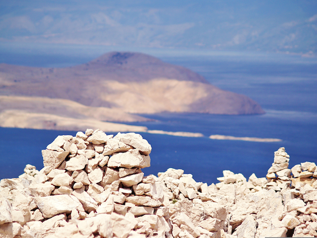 piled up rocks at the highest peak of the island Rab, Kamenjak, with sea in the background
