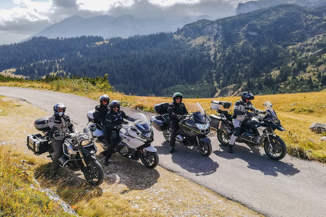 five-men-on-motorbikes-posing-for-a-photo-with-stunning-scenery-in-the-background