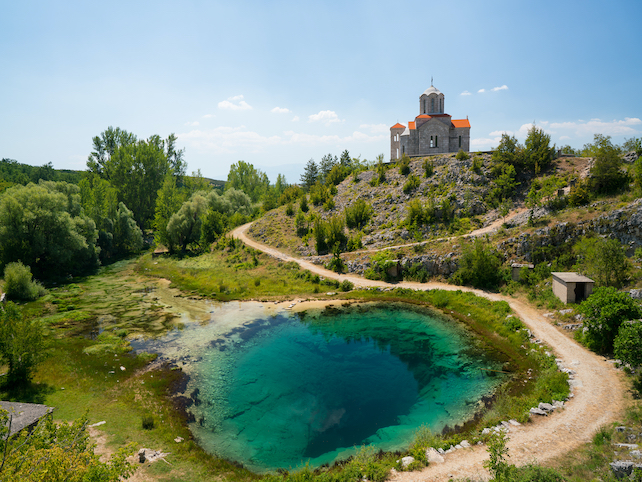 emerald-green-source-of-Cetina-River-in-Dalmatia-with-a-hill-and-church-in-the-background