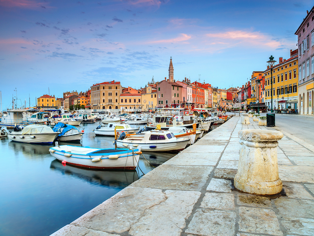 Small boats in the port of Rovinj overlooking the old city center during sunset