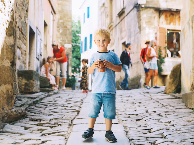 happy-smiling-child-holding-a-cup-on-a-narrow-cobble-street-in-Dalmatia