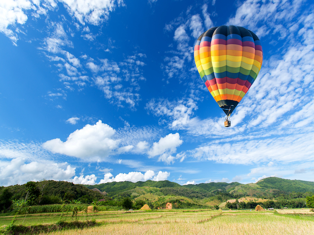 people-flying-in-a-hot-air-baloon-above-green-hills-and-fields-during-sunny-day