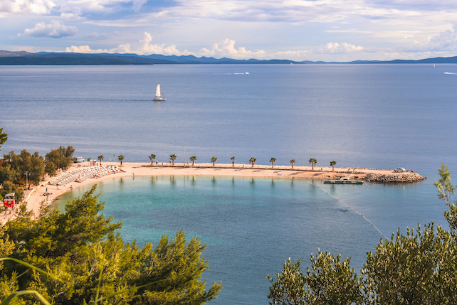 view-from-a-hill-at-a-sandy-beach-with-sun-loungers-and-palm-trees