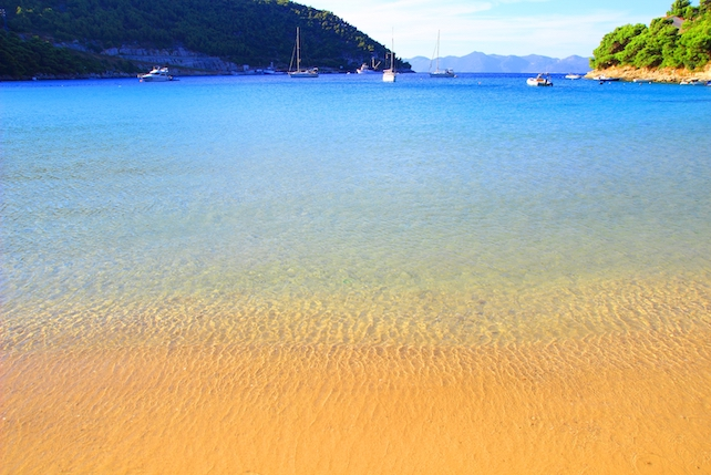 close-up-of-a-sandy-beach-with-shallow-water-and-a-hill-in-the-background