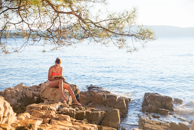 woman-in-red-swimsuit-reading-a-book-underneath-a-tree-on-a-rocky-beach-in-Croatia