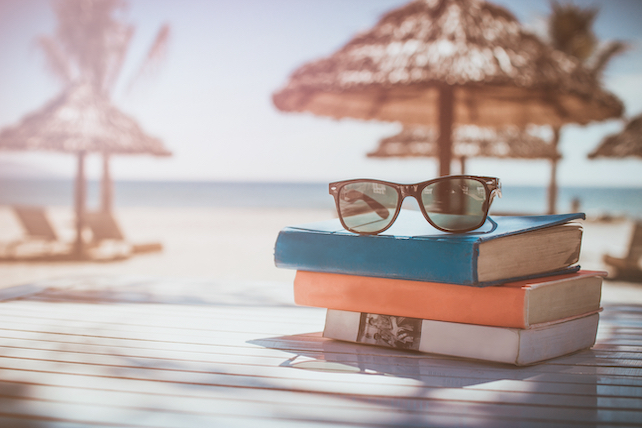 stack-of-books-and-sunglases-on-a-beach-table-with-sea-and-sun-umbrellas-in-the-distance