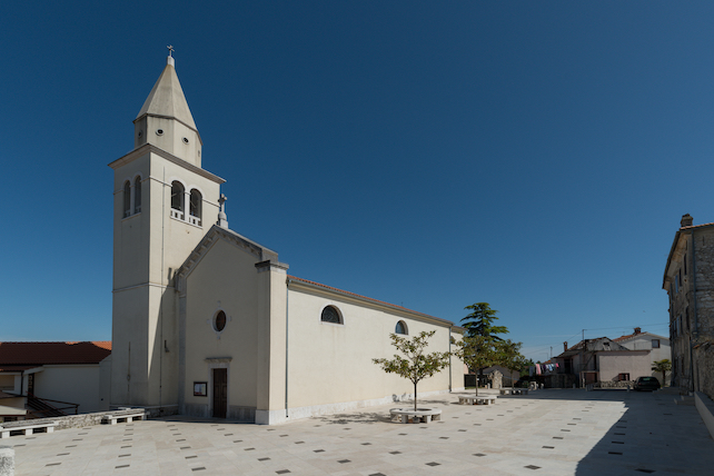 a-wide-square-in-Funtana-with-a-small-church-and-a-bell-tower-in-the-middle