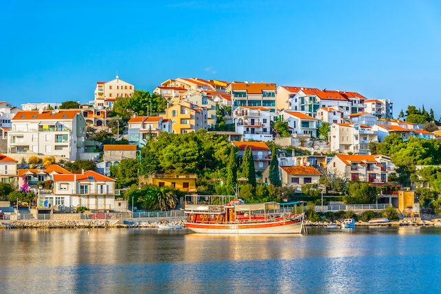 view-from-the-sea-of-Rogoznica-with-houses-on-the-hill-and-a-boat-in-harbour